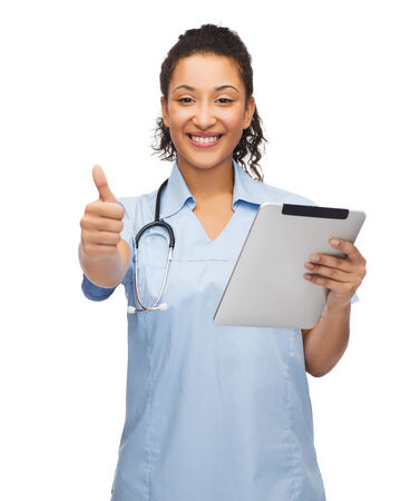 healthcare, technology and medicine concept - female african american doctor or nurse with stethoscope and tablet pc showing thumbs up photo