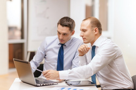 office presentation: business, technology and office concept - two businessmen with laptop, tablet pc computer and papers having discussion in office Stock Photo