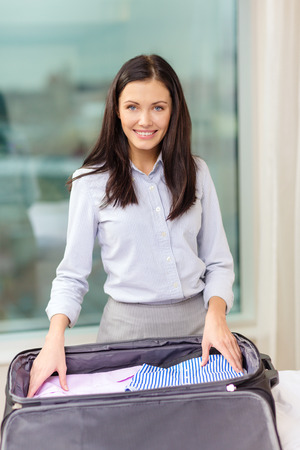business, technology, internet and hotel concept - happy businesswoman packing things in suitcase in hotel room Stock Photo