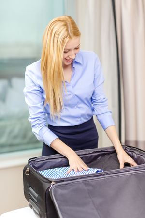 business, technology, internet and hotel concept - happy businesswoman packing things in suitcase in hotel room photo