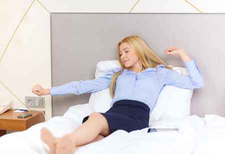 business, technology, internet and hotel concept - happy businesswoman lying in bed in hotel room Stock Photo