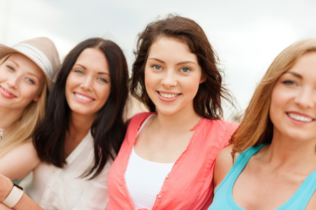 chilling: summer holidays and vacation concept - group of smiling girls chilling on the beach Stock Photo