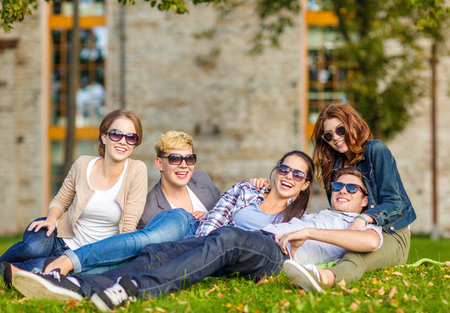 chilling: summer holidays, education, campus and teenage concept - group of students or teenagers hanging out outdoors