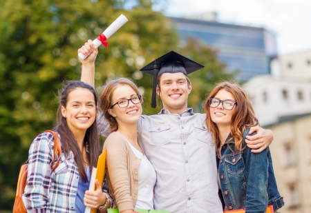 master degree: education, campus and teenage concept - group of students or teenagers with files, folders, eyeglasses and diploma Stock Photo