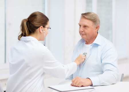 healthcare, medicine and elderly concept - female doctor or nurse with old man listening to heart beat Stock Photo
