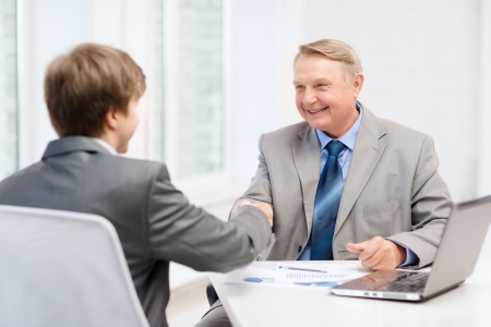 boss and employee: business, technology and office concept - older man and young man shaking hands in office