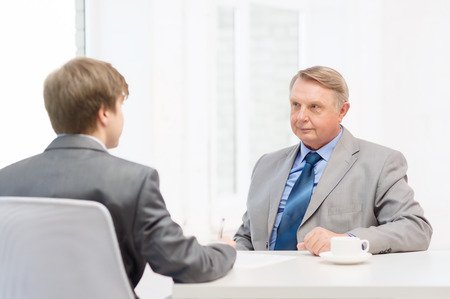 business, technology and office concept - older man and young\ man signing papers in office