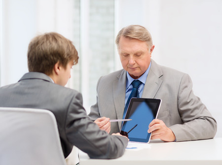 business, advertisement, technology and office concept - older man and young man with tablet pc computer in office photo