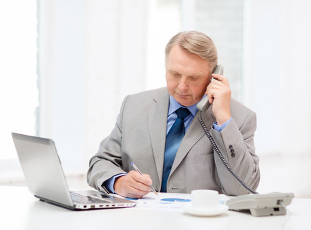 business, technologym communication and office concept - busy older businessman with laptop, charts, coffee and telephone in office photo
