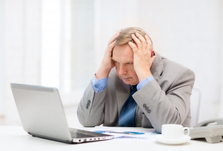 unhappy worker: business, technologym communication and office concept - upset older businessman with laptop, charts, coffee and telephone in office