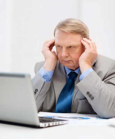 business, technology and office concept - upset older businessman with laptop and charts in office photo