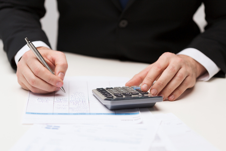 business and office concept - close up of businessman with papers and calculator photo