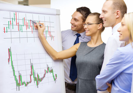 flip chart: business, money and office concept - smiling business team with forex chart on flip board having discussion
