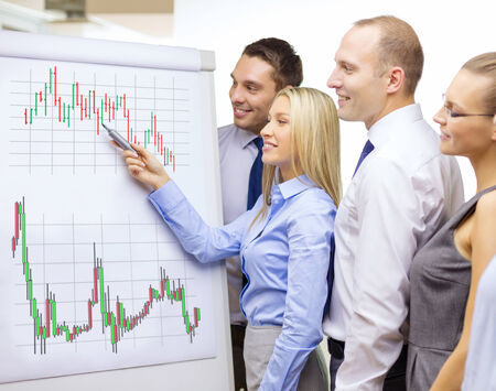 business, money and office concept - smiling business team with forex chart on flip board having discussion Stock Photo - 25545705