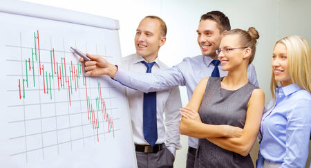 business, money and office concept - smiling business team with forex chart on flip board having discussion Stock Photo - 25545704