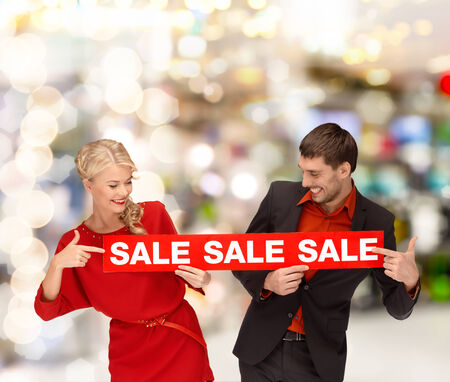shopping, sale, christmas, couple and mall concept - smiling woman and man pointing finger to red sale sign at shopping mall photo