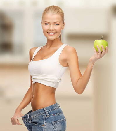 diet and sport concept - sporty woman showing big pants and apple in kitchen Imagens