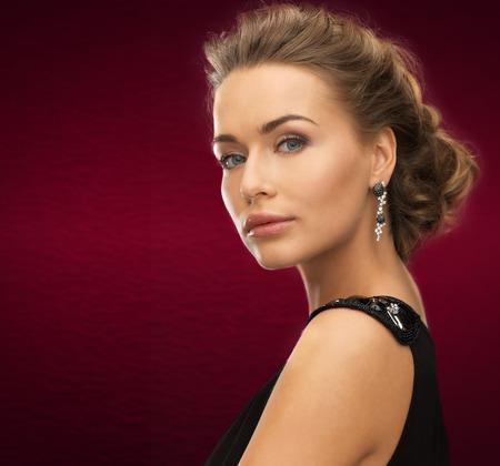 jewelry and beauty concept - beautiful woman in evening dress wearing diamond earrings photo