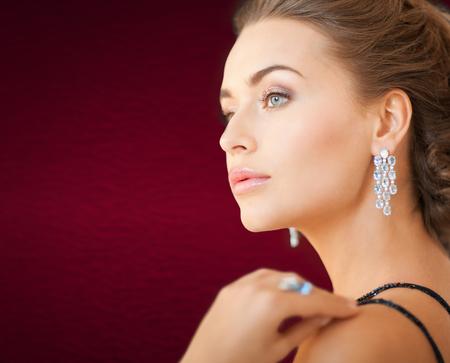 ear rings: jewelry and beauty concept - beautiful woman in evening dress wearing diamond earrings