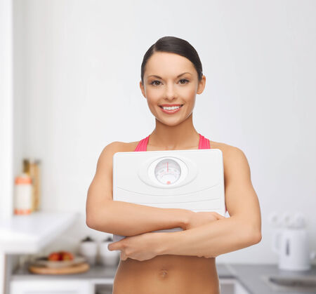 diet and sport concept - beautiful sporty woman with scale in kitchen Stock Photo