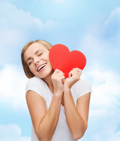 happiness, health and love concept - smiling woman in white t-shirt with heart photo