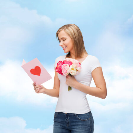 love, holidays and happiness concept - smiling girl with postcard and bouquet of lowers photo