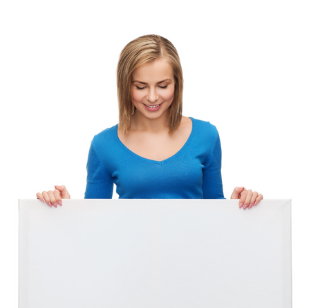 advertisement and people concept - smiling girl looking down at blank white board