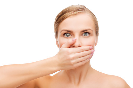 mouth: health and beauty concept - clean face of beautiful young woman covering her mouth with hand