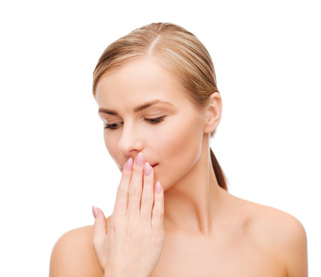 healthy mouth: health and beauty concept - clean face of beautiful young woman covering her mouth with hand