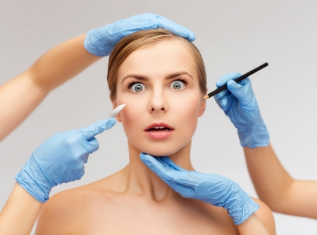 plastic surgeon: healthcare, beauty and medicine concept - beautiful woman face and beautician hands with pencil and scalpel