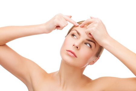 skin problem: health and beauty concept - face of beautiful young woman squeezing acne spots Stock Photo