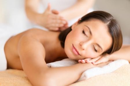 masoterapia: la salud, la belleza, la estación y el concepto de relajación - hermosa mujer con los ojos cerrados en el salón de spa recibiendo masaje Foto de archivo