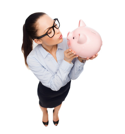 business, banking, investment and office concept - laughing businesswoman in eyeglasses sendink kisses to piggy bank photo