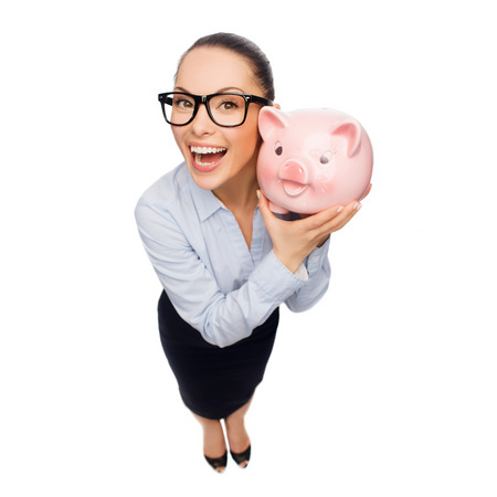 business, banking, investment and office concept - laughing businesswoman in eyeglasses with piggy bank photo