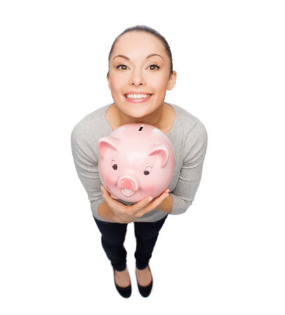 thrifty: banking and investment concept - smiling woman with piggy bank