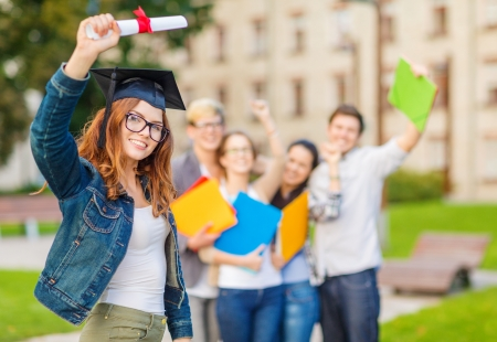education, campus and teenage concept - smiling teenage girl in corner-cap and eyeglasses with diploma and classmates on the back photo