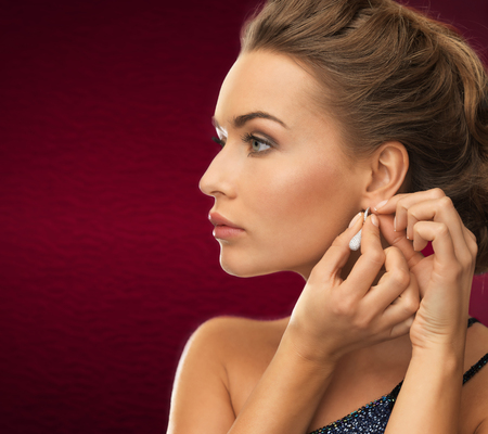 putting on: jewelry and beauty concept - close up of beautiful woman wearing shiny diamond earrings