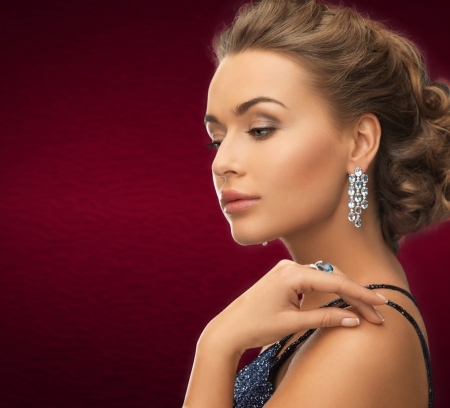 ear rings: jewelry and beauty concept - beautiful woman in evening dress wearing diamond earrings and ring