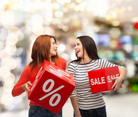 shopping, sale, mall and gift sconcept - two smiling teenage girls with percent and sale sign on red box at shopping mall photo