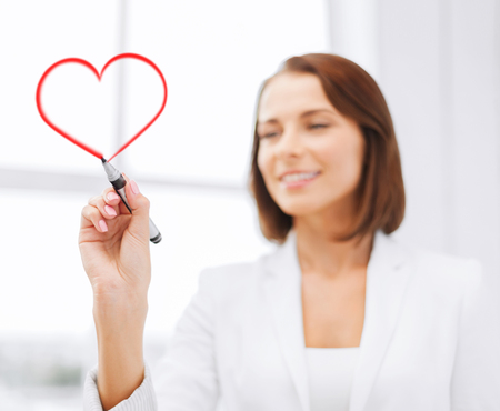 office, business and technology concept - businesswoman drawing heart in the air with marker photo
