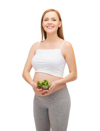 pregnancy, motherhood and happiness concept - happy future mother with bowl of salad photo