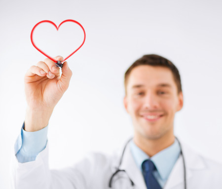 heart doctor: medicine, health and hospital concept - male doctor drawing heart in the air with marker Stock Photo