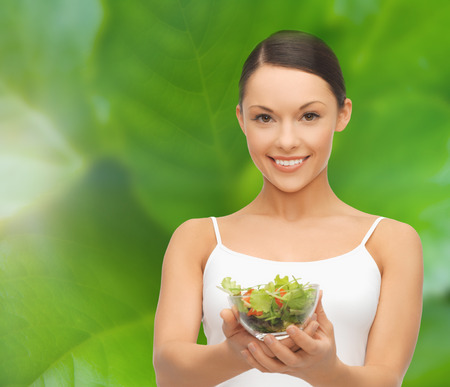 diet and sport concept - healthy woman holding bowl with salad photo
