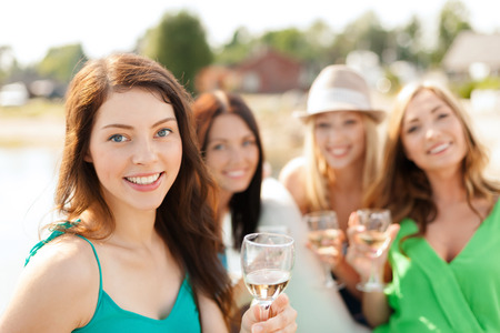 summer holidays, vacation and celebration concept - smiling girls with champagne glasses Stock Photo