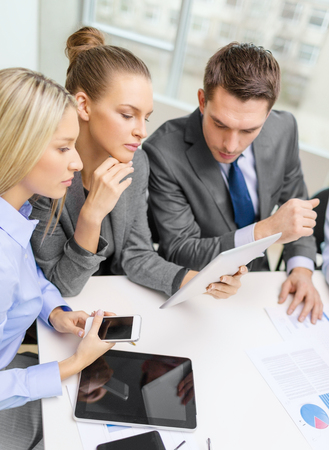 business, technology and office concept - serious business team with tablet pc, documents and smartphones having discussion in office photo