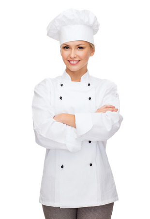 arms crossed: cooking and food concept - smiling female chef, cook or baker with crossed arms