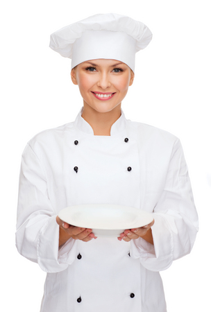 female chef: cooking and food concept - smiling female chef, cook or baker with empty plate