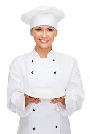 gorro chef: la cocina y el concepto de alimentos - sonriendo mujer chef, cocinero o panadero con la placa vacía