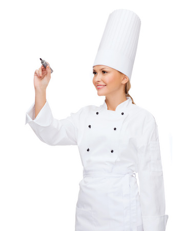 cooking, new techology , advertisement and food concept - smiling female chef with marker writing something on virtual screen photo