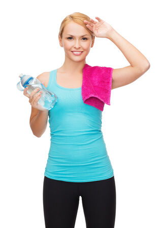 athletic wear: sport, excercise and healthcare - sporty woman with pink towel and water bottle Stock Photo